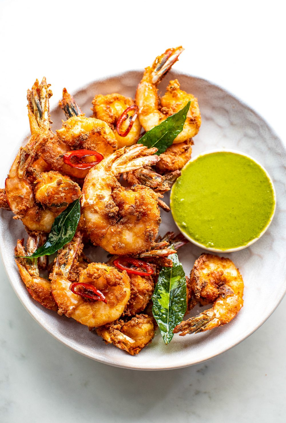 Prawns Koliwada with green chutney in a bowl